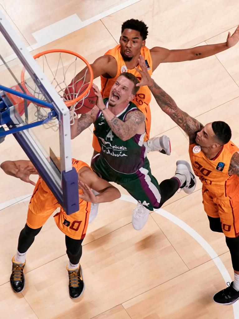 Adams intenta anotar bajo el aro rival rodeado de defensores